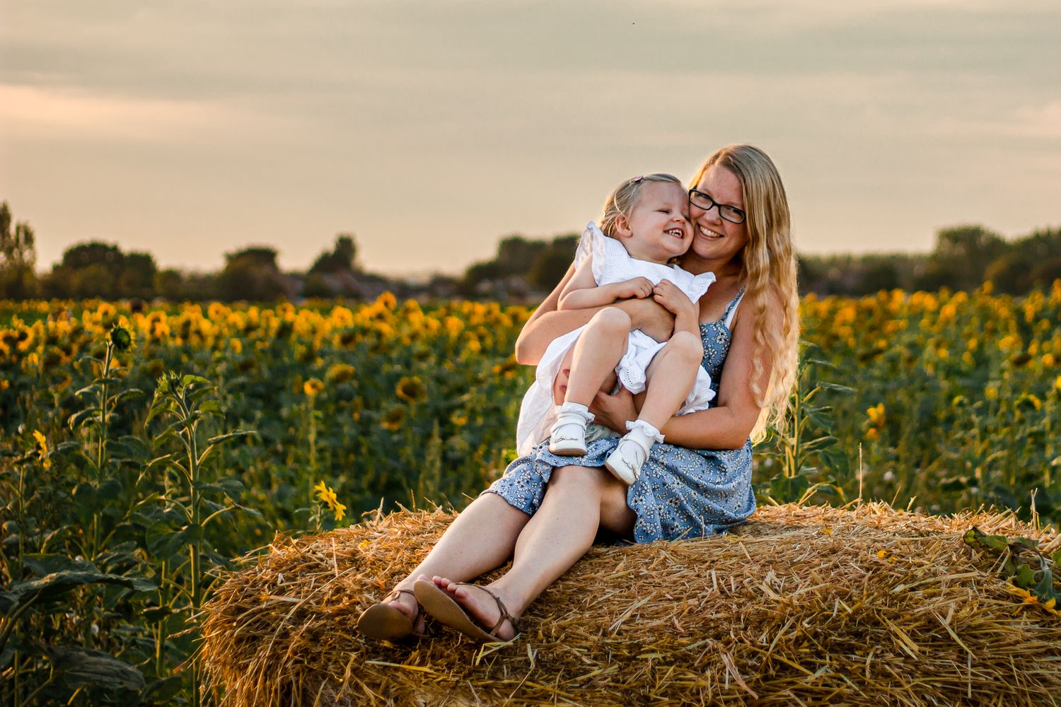 In a sunflower field on Hayling Island a Mum sits on a hay bale laughing with her 2 year old.
