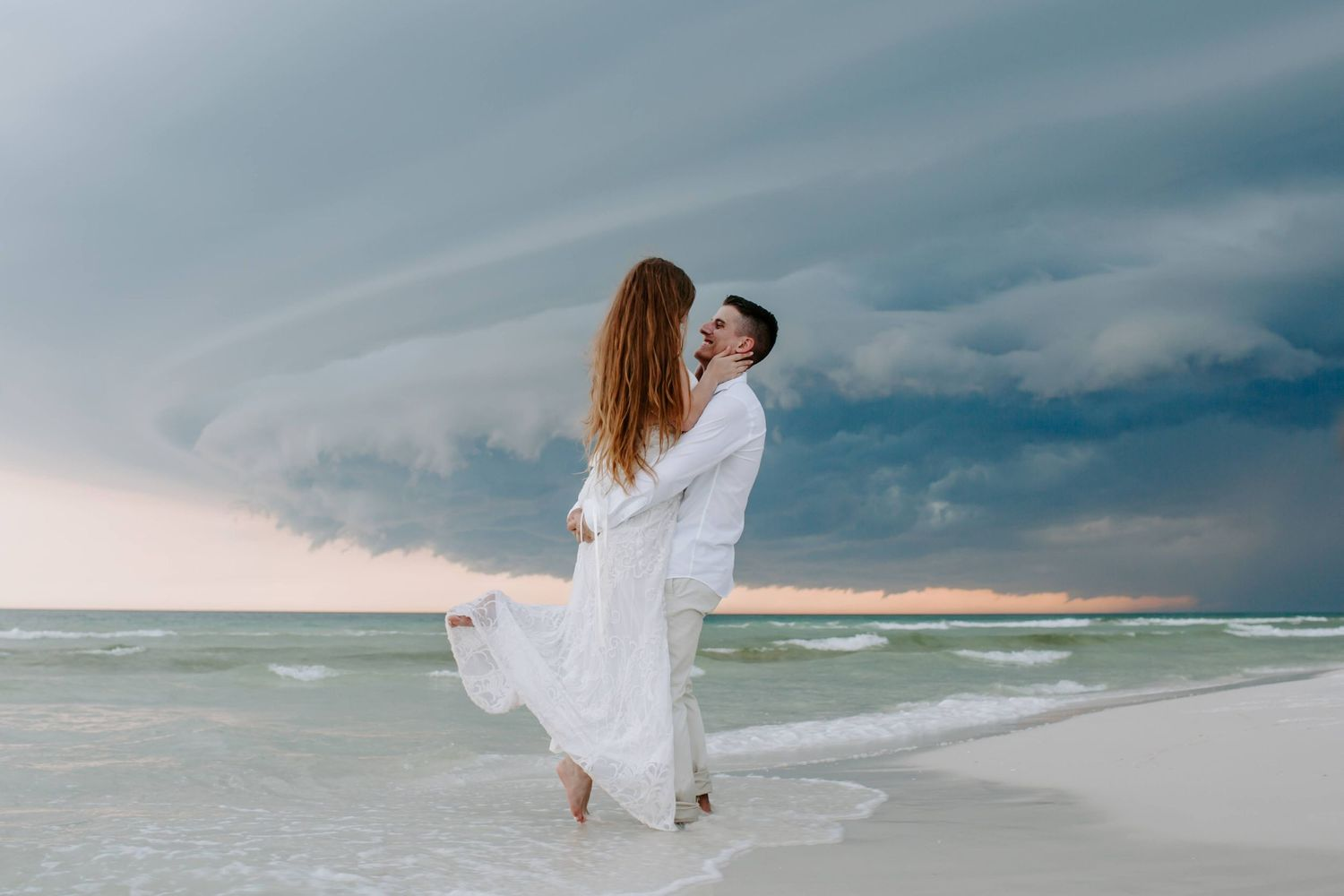 man holding his new bride while a storm brews in the background during their Destin elopement