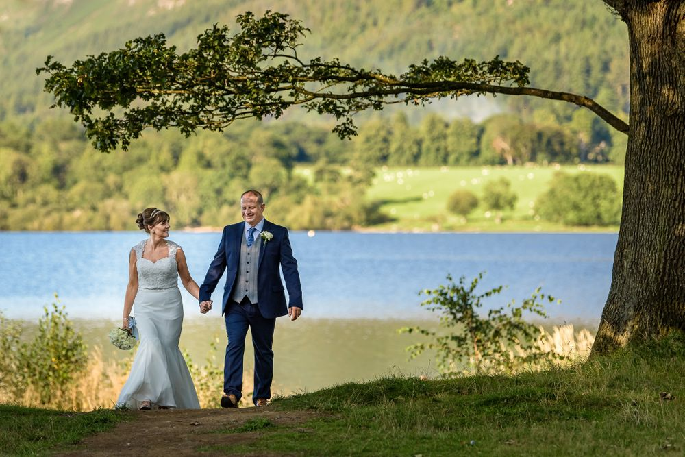 Briude and groom under trees at Bassenthwaite Lake