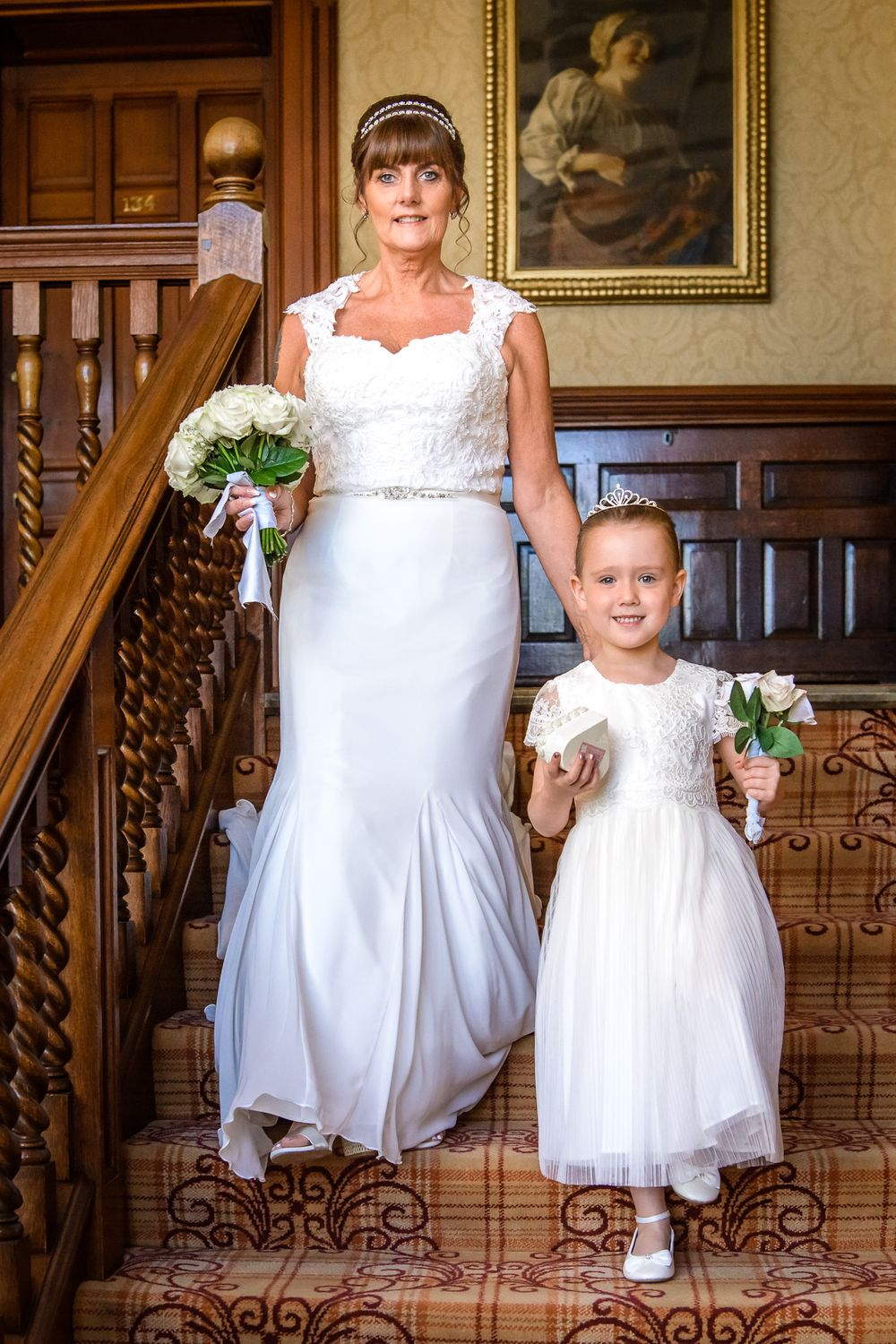 Bride and flower girl coming down stairs at Armathwaite Hall