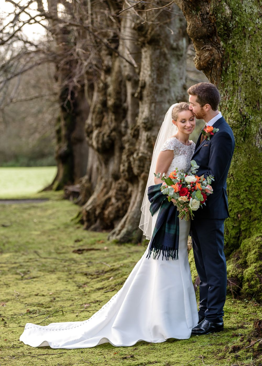 Bride and groom in avenue of trees at Armathwaite Hall