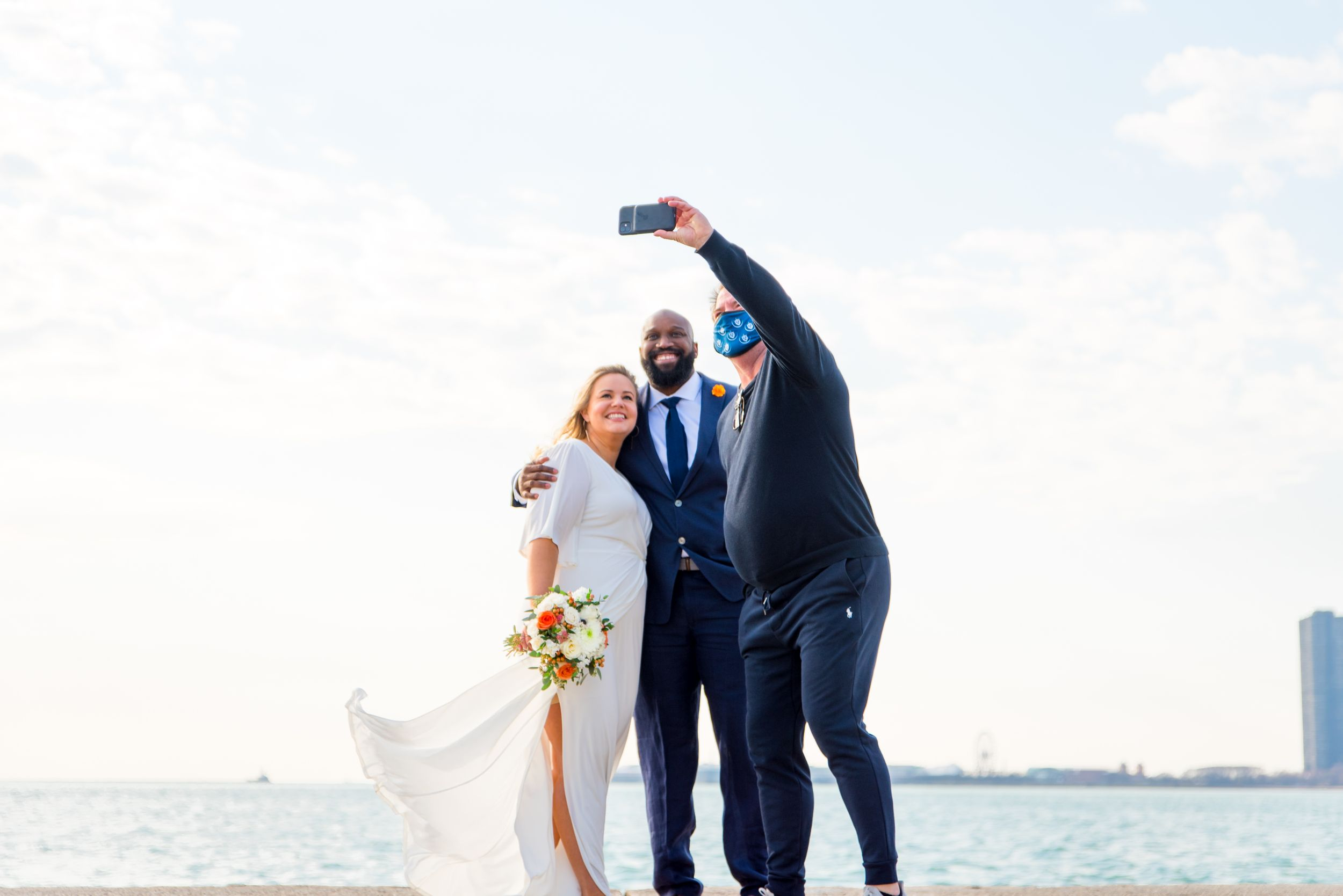 wedding pictures at north avenue beach chicago couple taking selfie with someone passing by