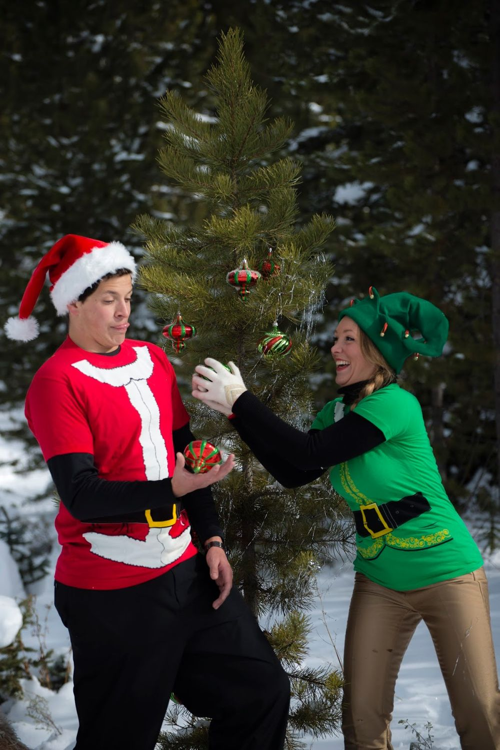 A couple in Christmas costumes tossing Christmas ornaments