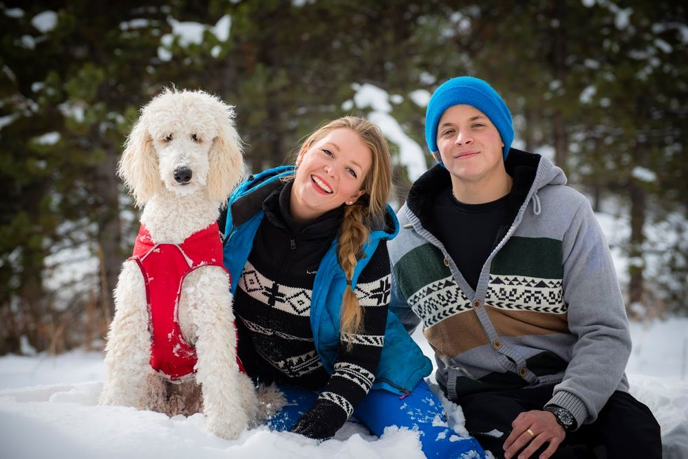A couple and their poodle sitting in the snow