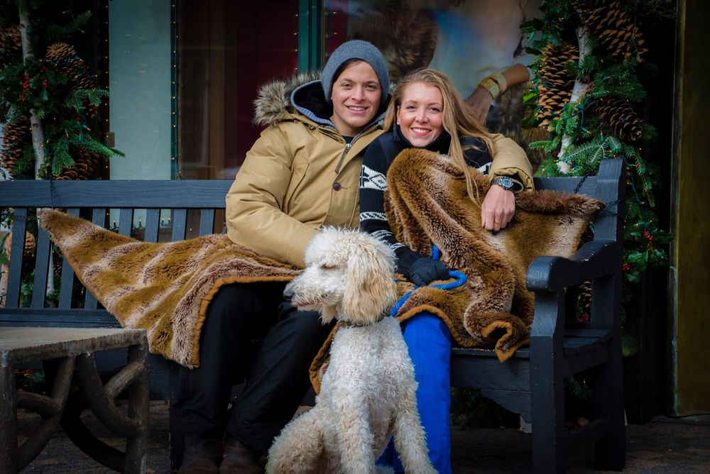 A couple and their poodle bundled up on a bench in Vail Villgae