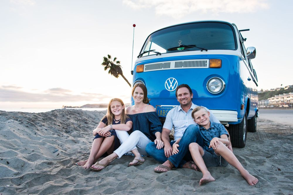 Photo of a family in front of a VW Bus on the beach in Orange County, CA