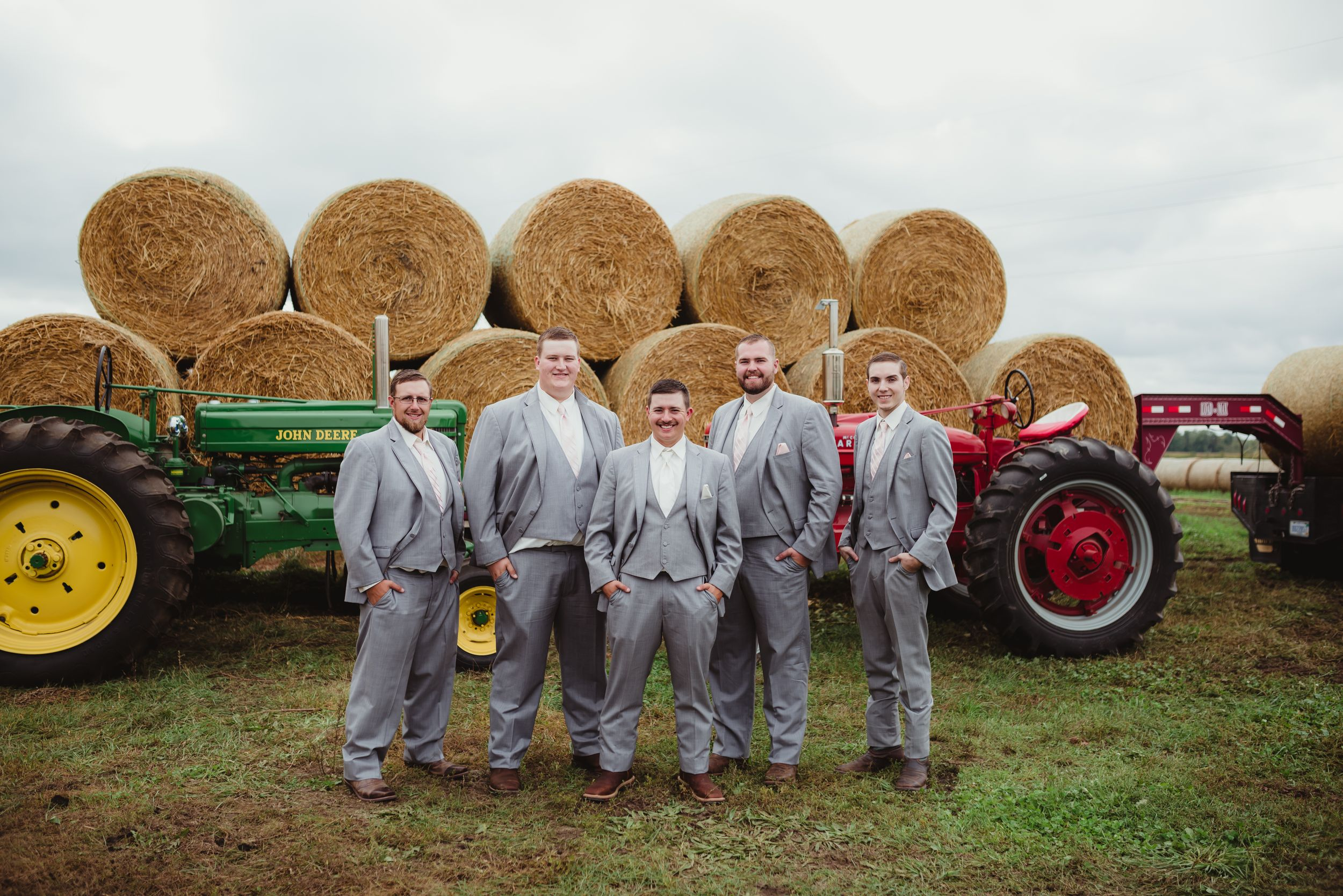 Groom and groomsmen in front of a tractor and rolls of hay. They wear light grey suits.