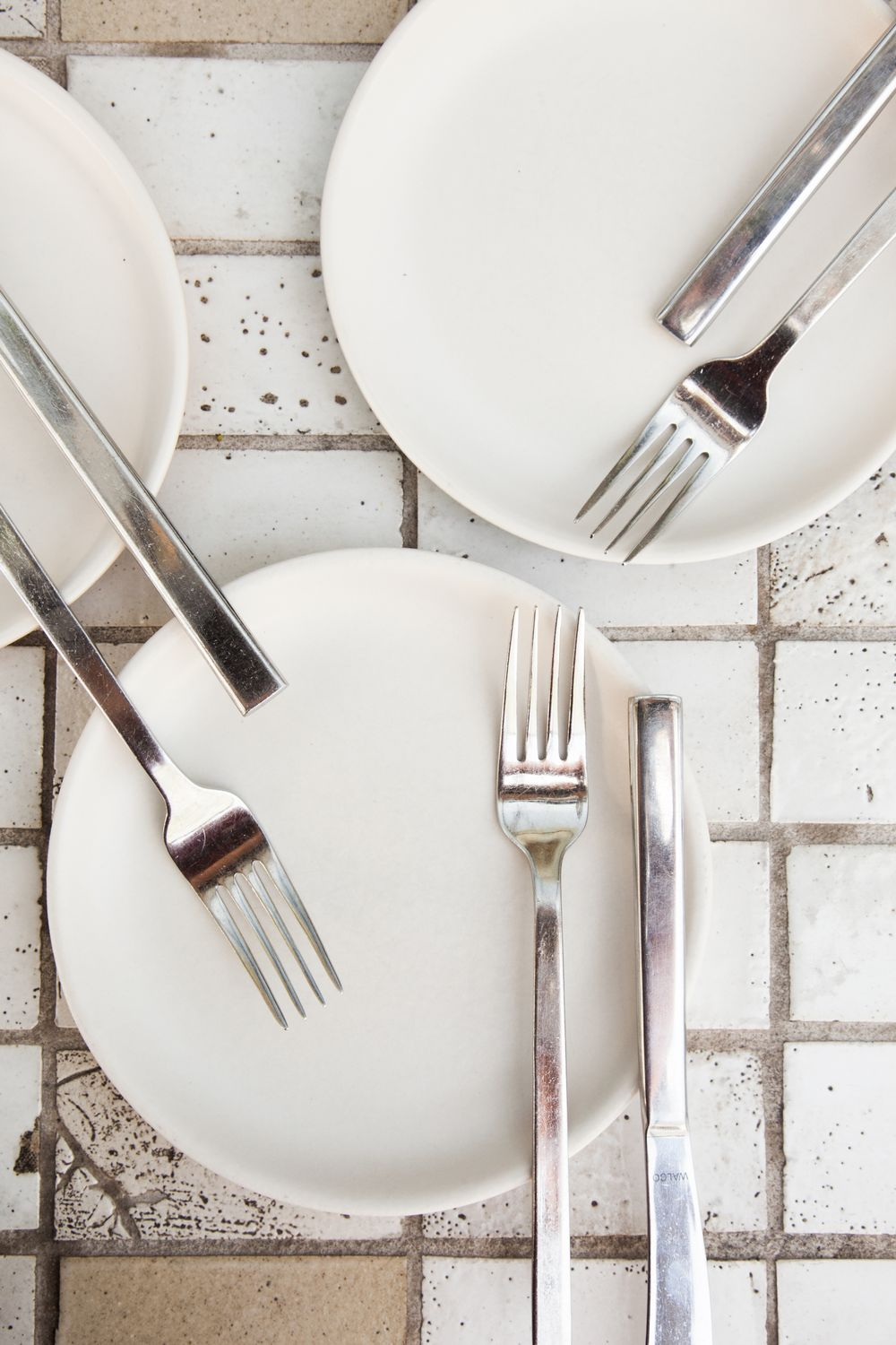 graphic minimal white plates with forks on white brick in restaurant