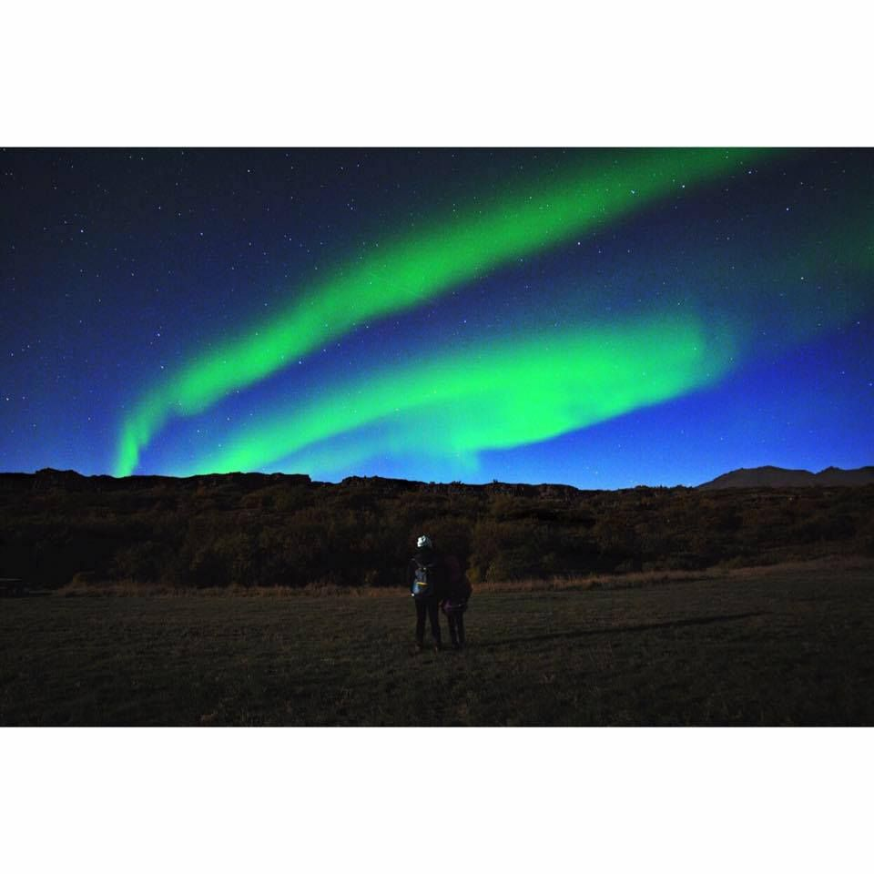 A mother and daughter look at the the northern lights or Aurora borealis in a field with mountain Mosfellsdalur, Iceland