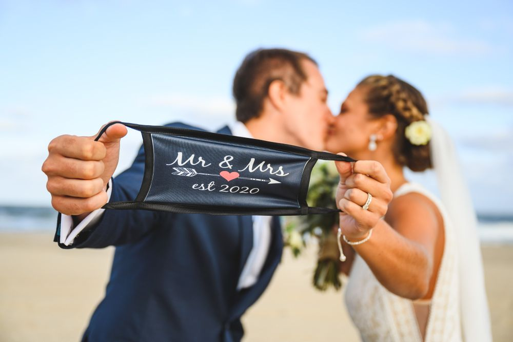 bride and groom kissing behind their protective mask on LBI beach