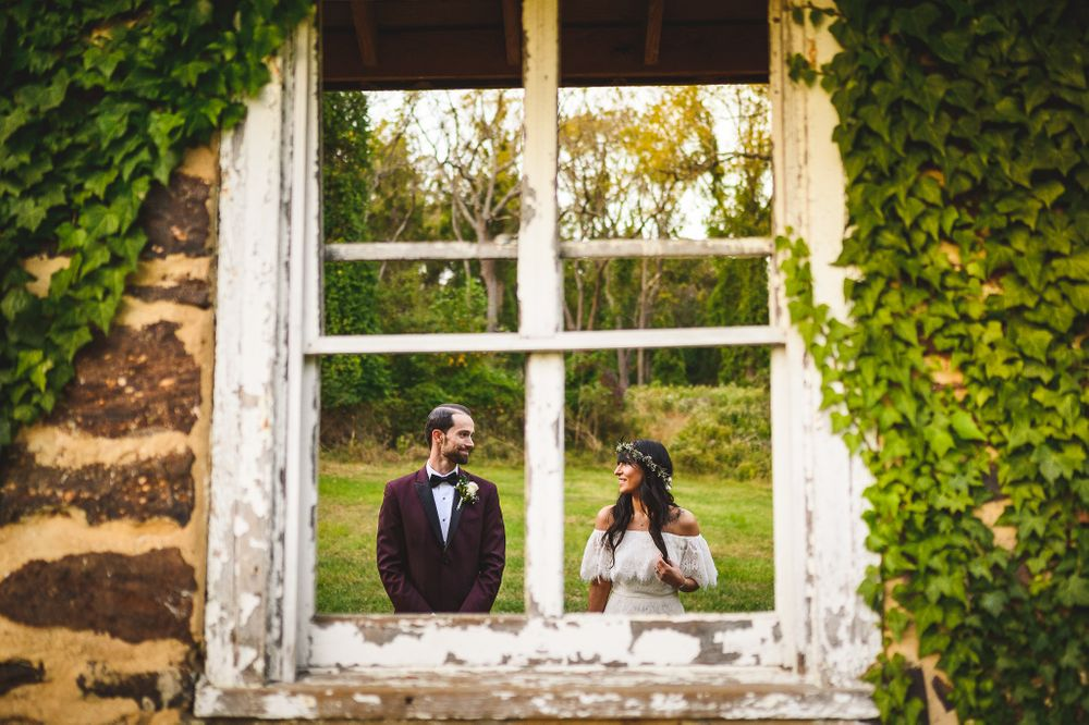 bride and groom smiling at each other through window wall at claypit creek park