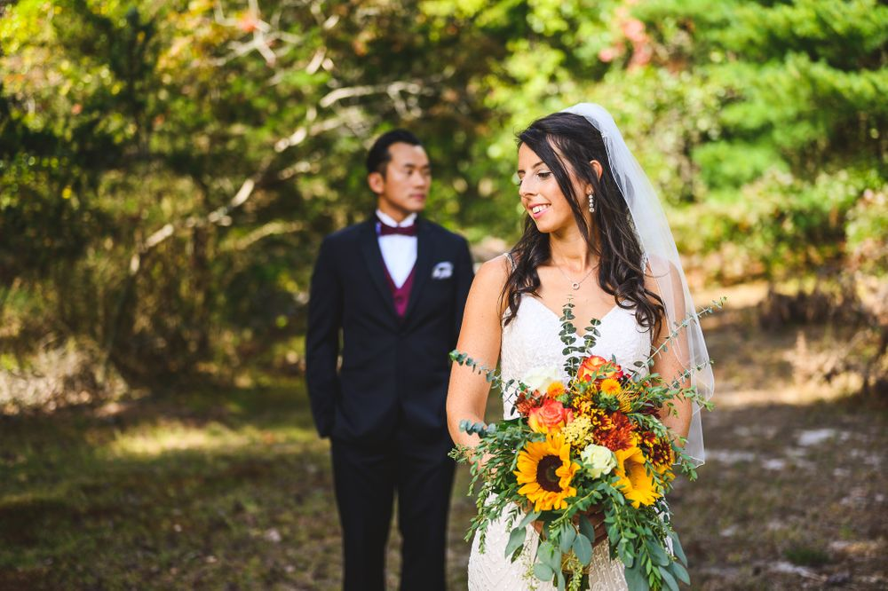 bride in front of groom holding her flowers at double trouble state park