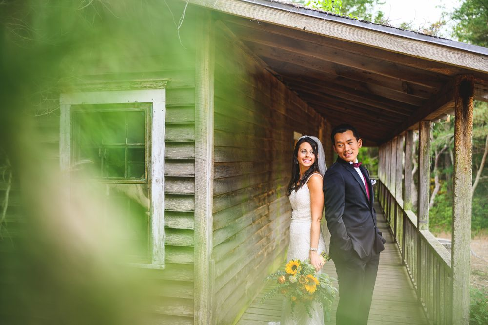 bride and groom standing back to back smiling on a old porch at double trouble state park