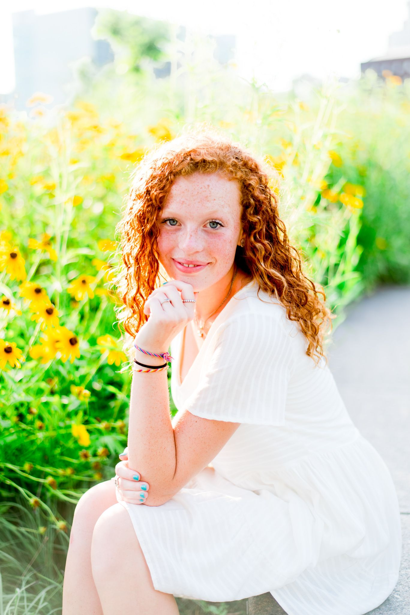 young woman with red curly hair in white dress sitting on concrete bench in front of black eyed susans at Smale Park