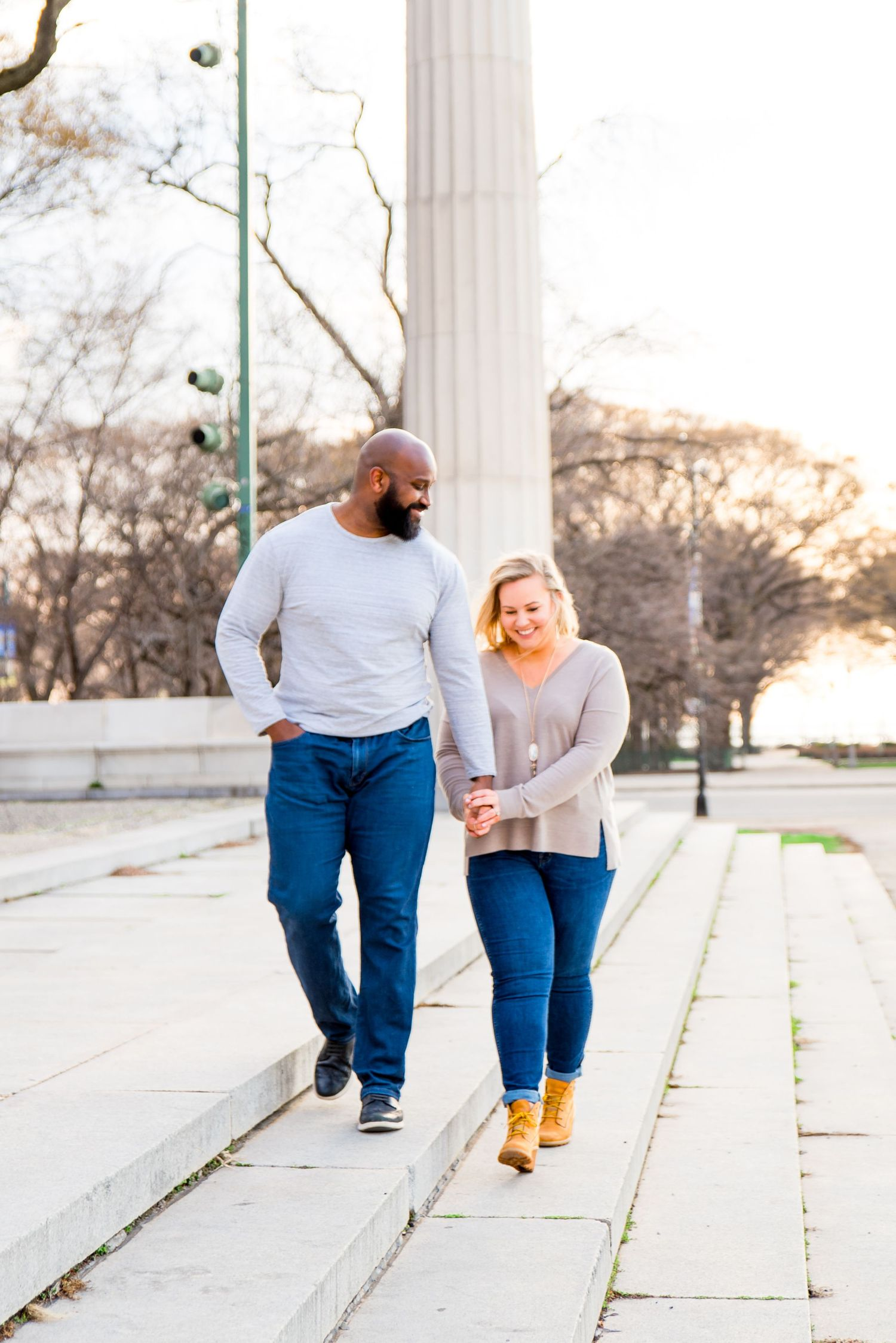 man and woman holding hands laughing in Grant Park sunrise engagement pictures in Chicago