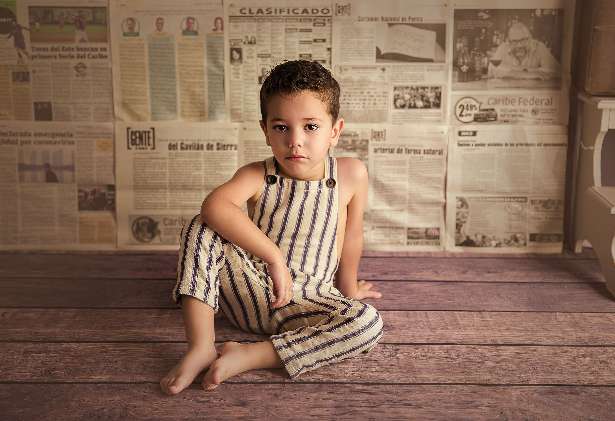 child sitting on wood floor wearing overalls newspaper backdrop