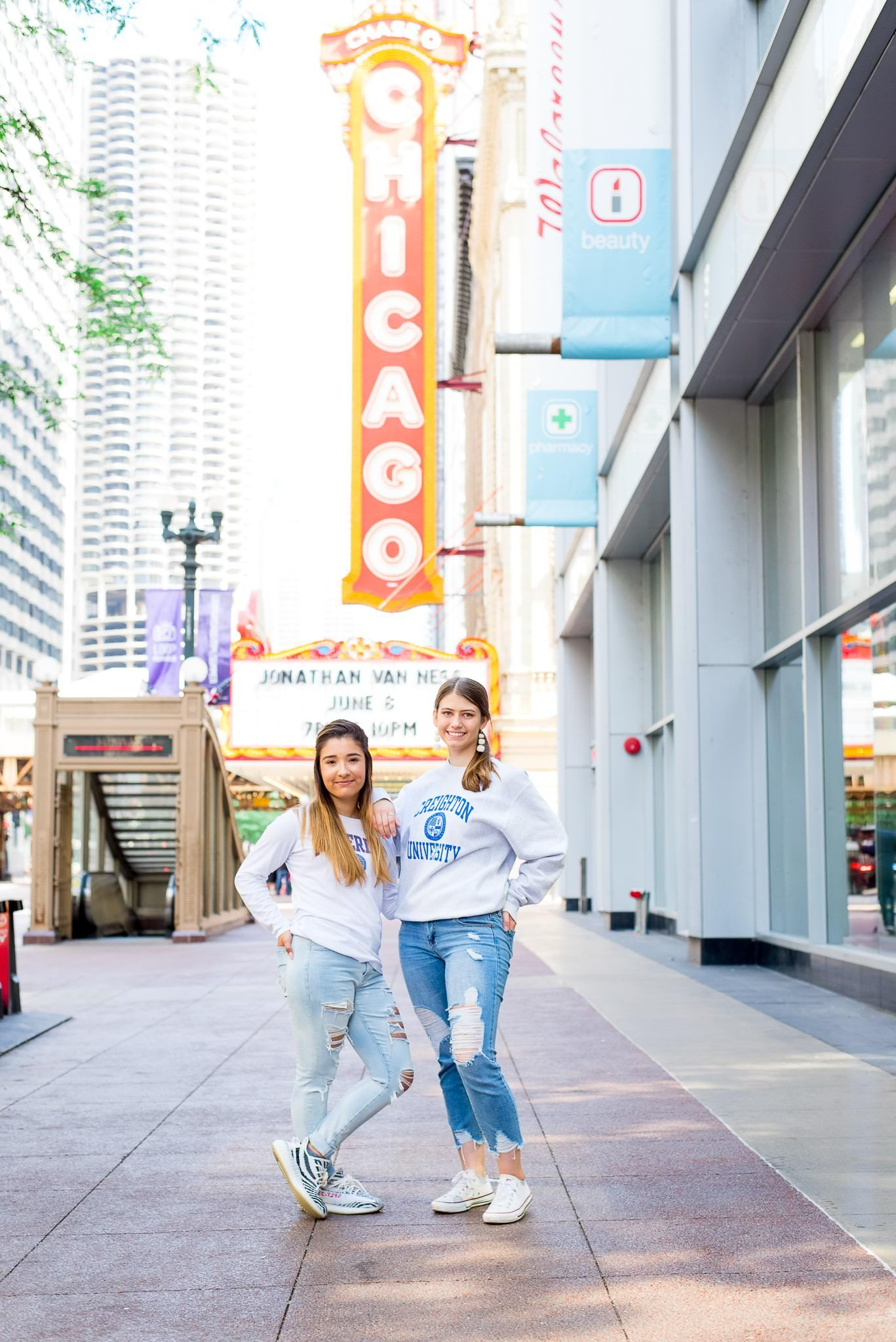 two senior girls in front of the Chicago Theater sign for Chicago senior pictures back to back
