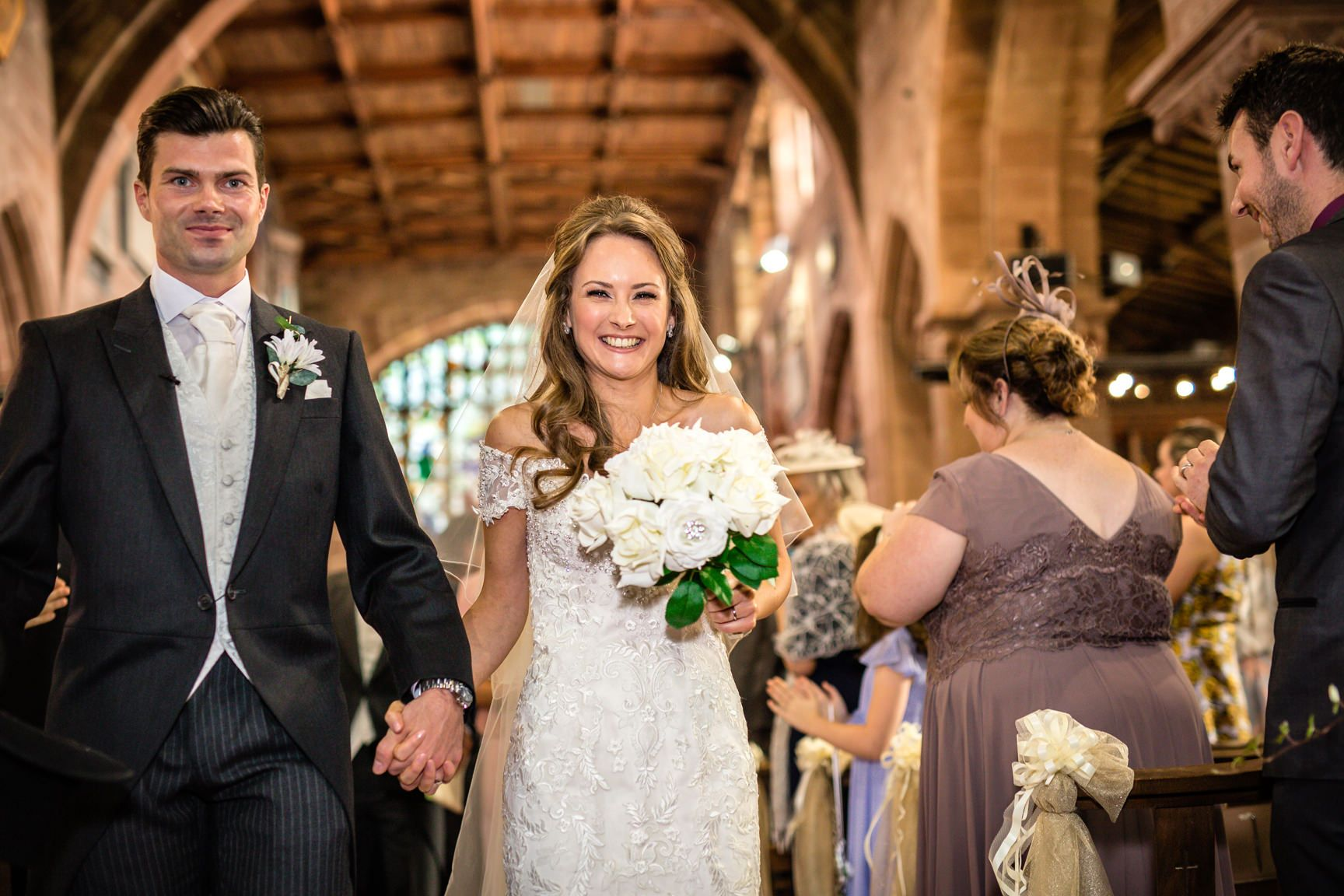 Groom with his bride holding a bouquet of flowers walking up the aisle on their Willington Hall wedding day