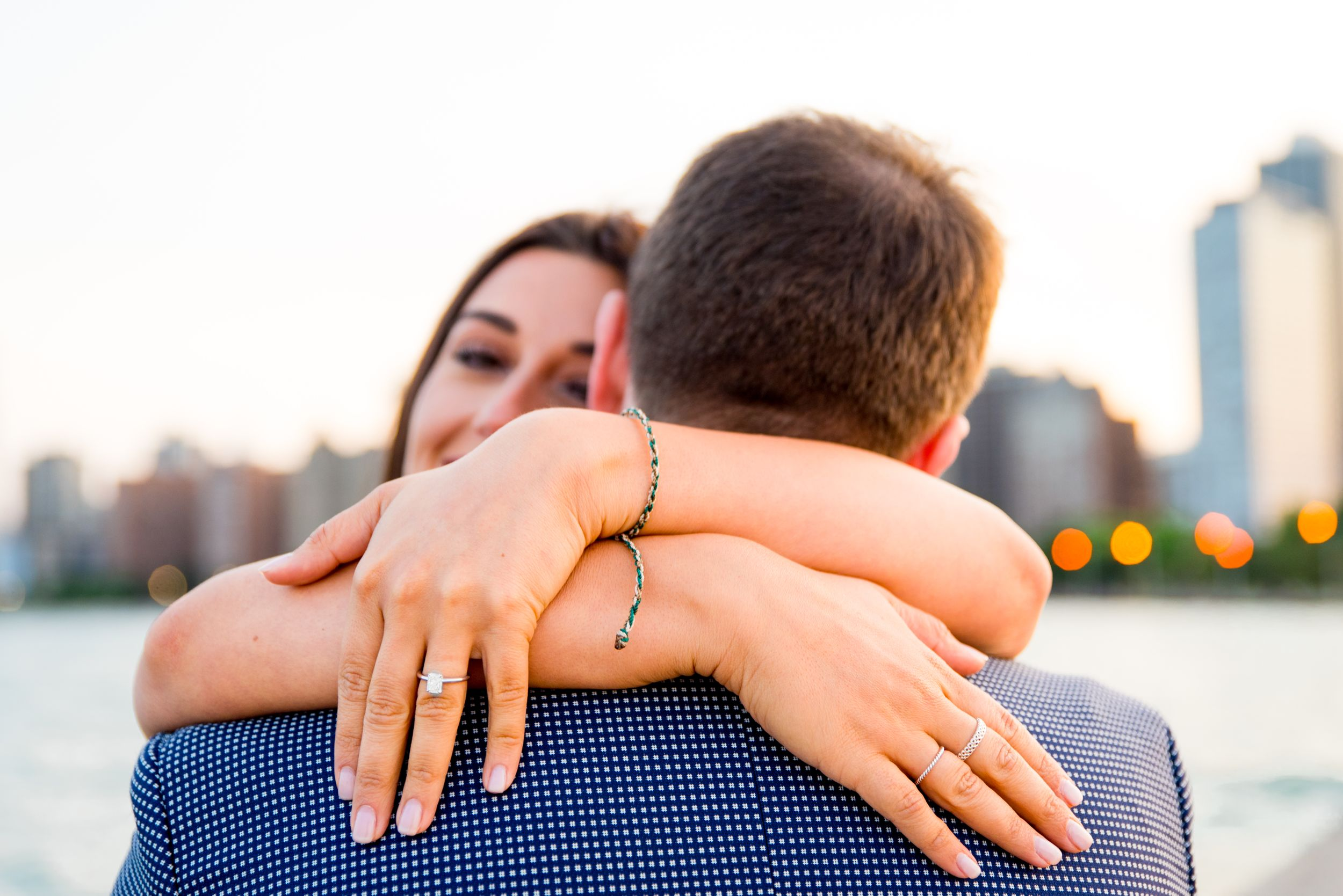 woman hugging new fiance showing off her ring and peeking over his shoulder