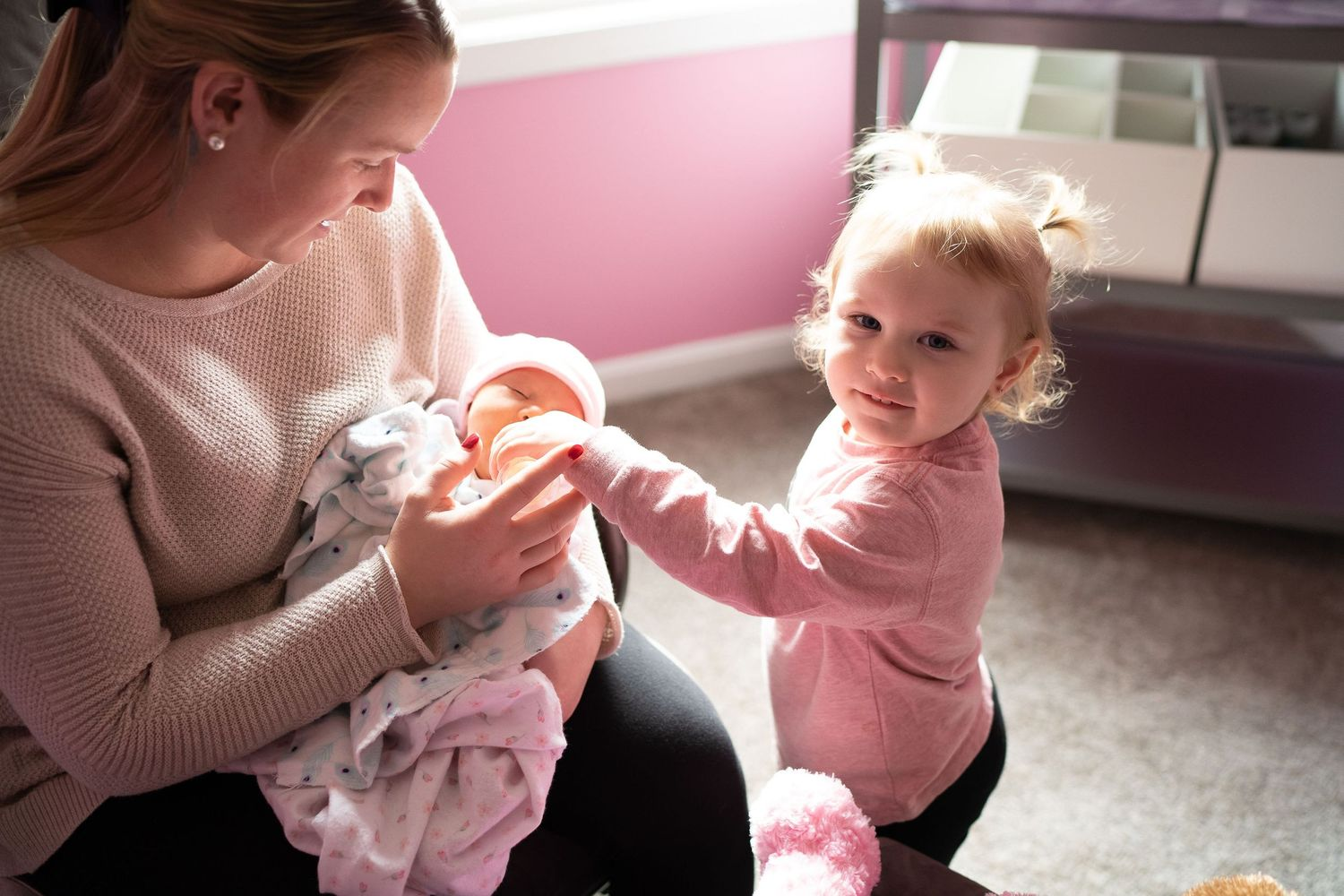 toddler helping feed her baby sister in sudbury ma home