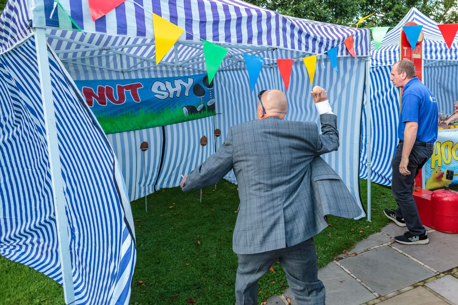 wedding guest has a go at the coconut shy at the bride and grooms funair at ribby village hall