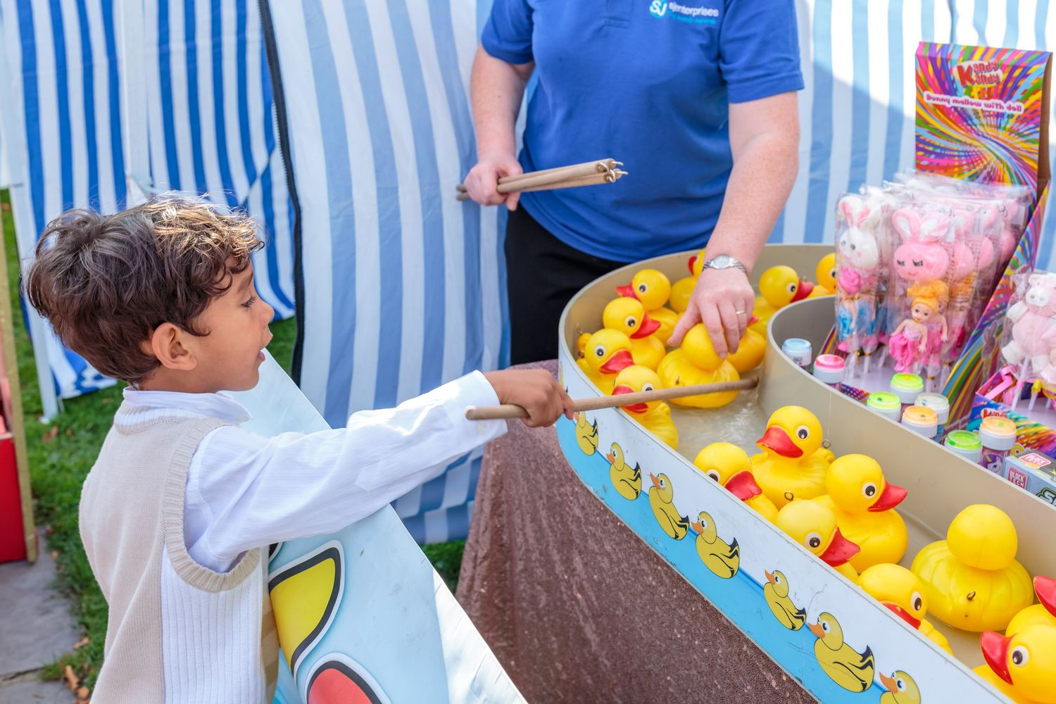young boys plays hook a duck at the bride and grooms ribby hall funfair