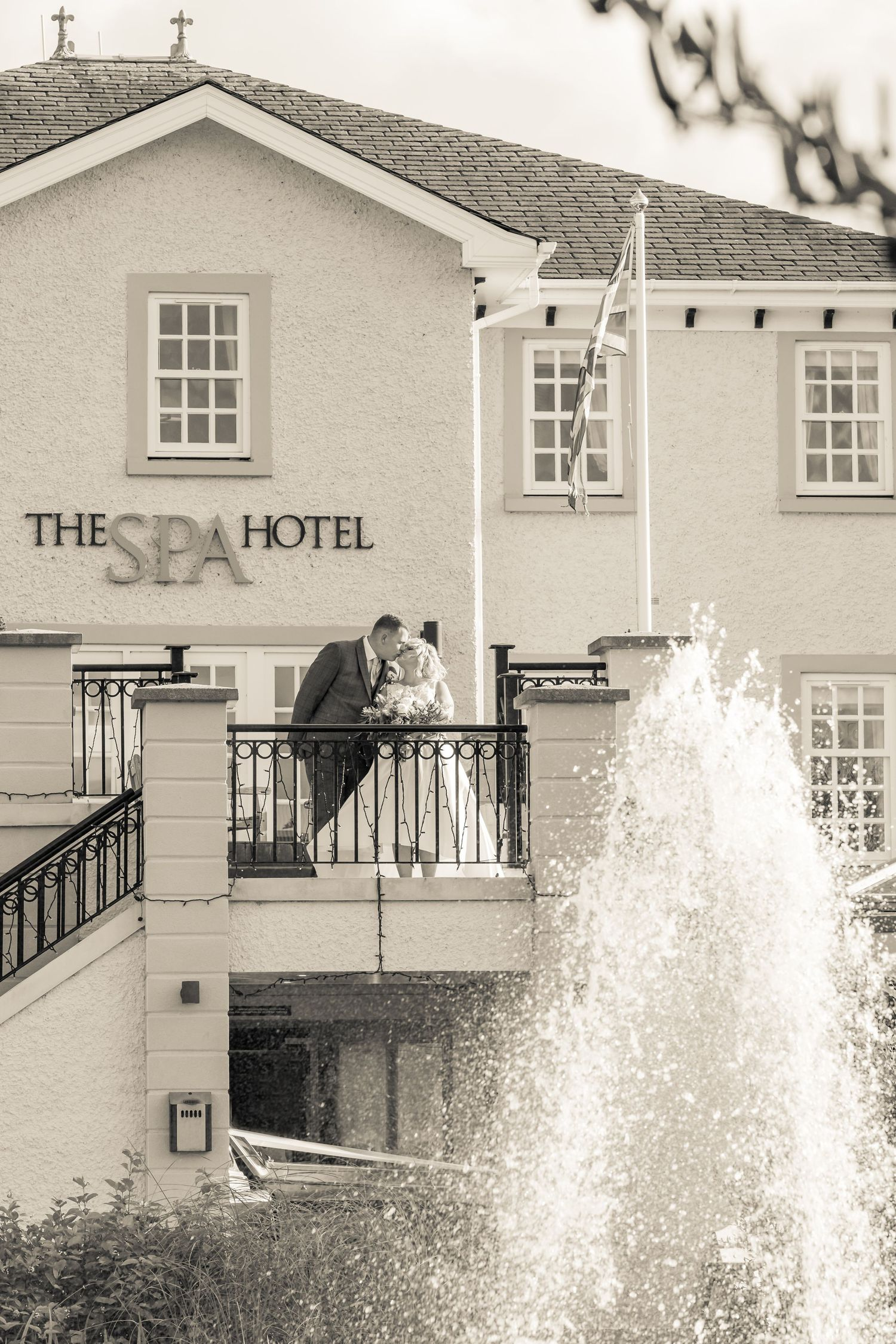 bride and groom pose for a photograph on the stairs outside ribby hall spa hotel water fountain in the foreground