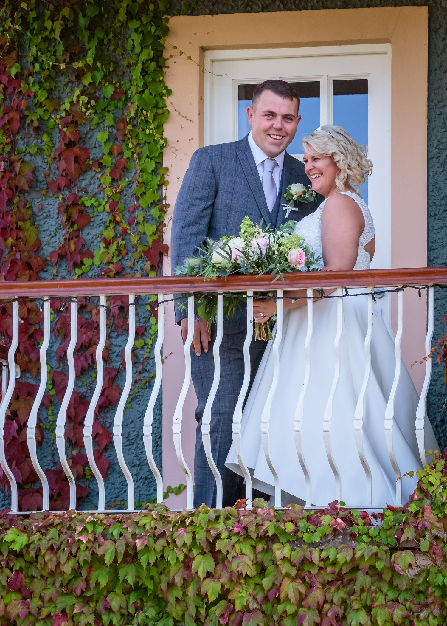 bride and groom portrait on the ivy covered balcony at ribby hall spa hotel