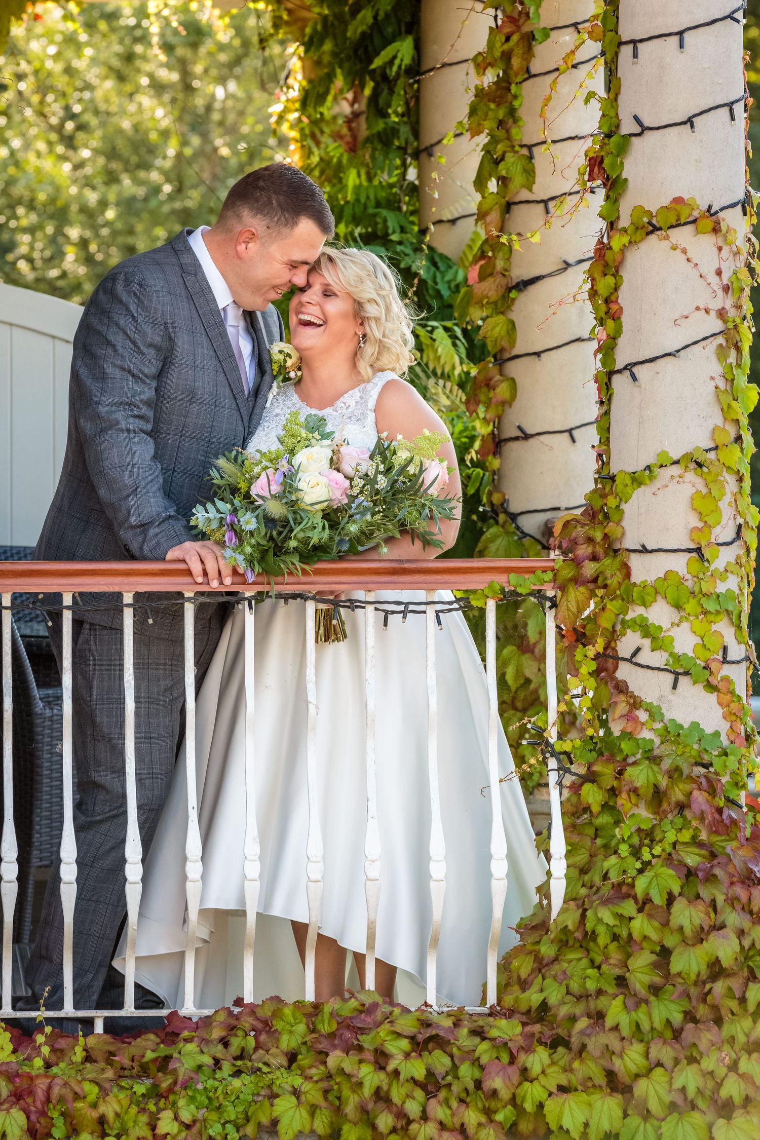 cute shot of the groom smiling and the bride laughing as they touch heads on the ivy covered ribby hall balcony