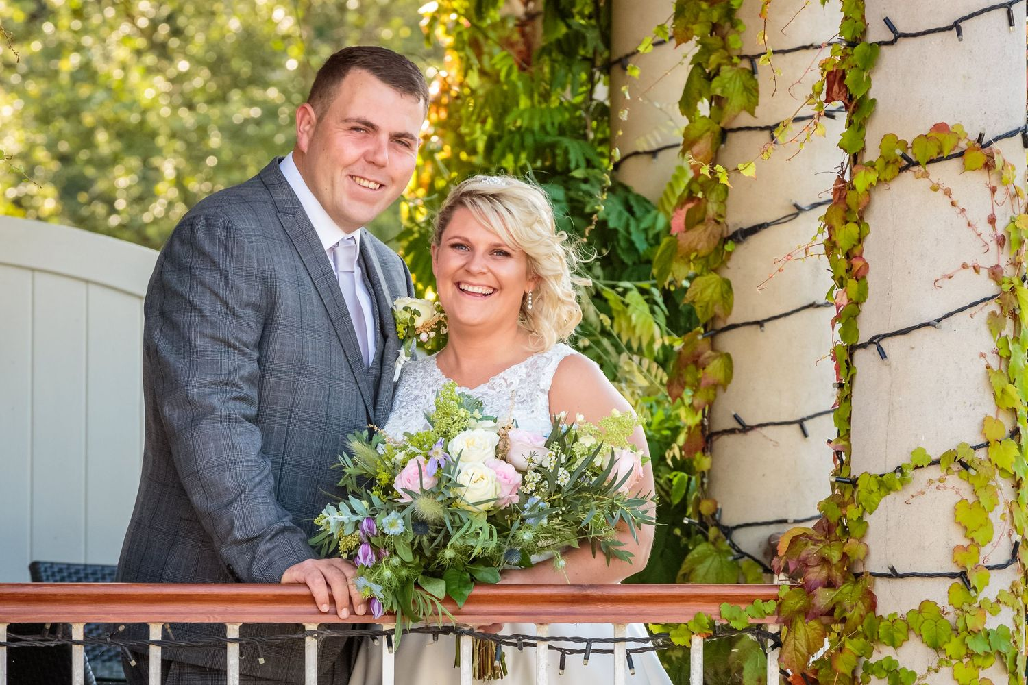 relaxed photo of the bride and groom smiling lean on the balcony rail pillars behind them wrapped in fairy lights