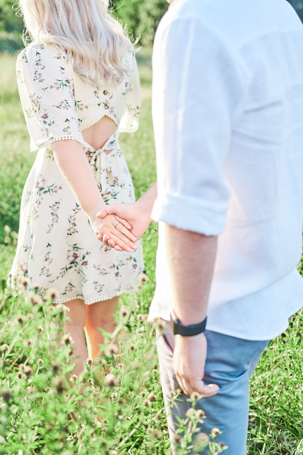 beautiful couple hold hands walking through wildflower meadow for engagement shoot at Catton Park, Norwich