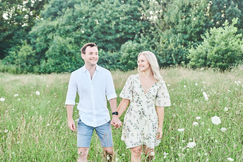 beautiful couple walk through wildflower meadow for engagement shoot at Catton Park, Norwich