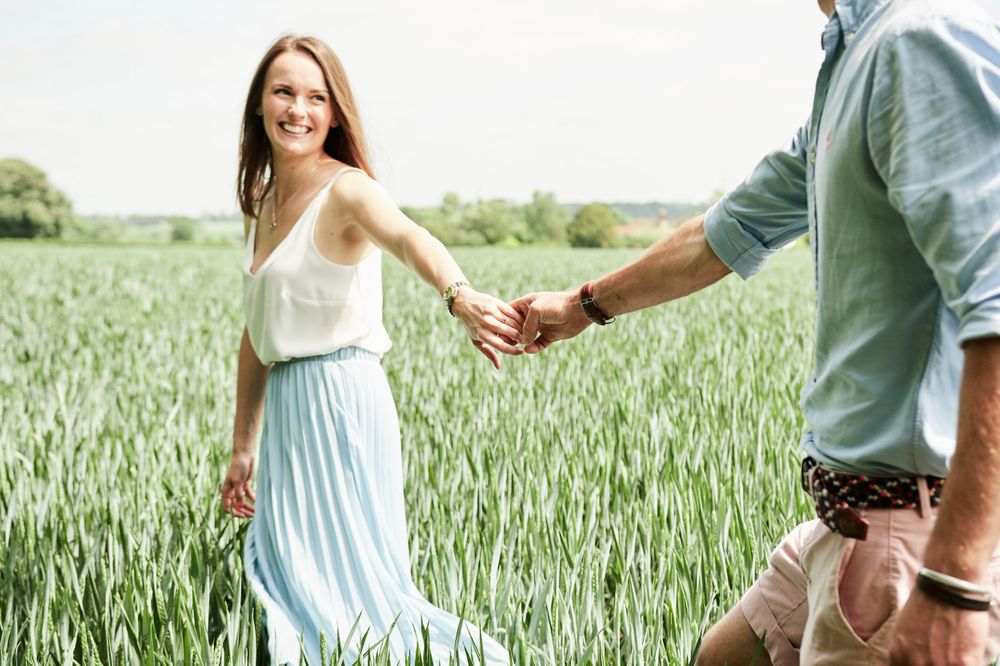 newly engaged couple walk through barley field holding hands by Norfolk wedding photographer Faye Amare