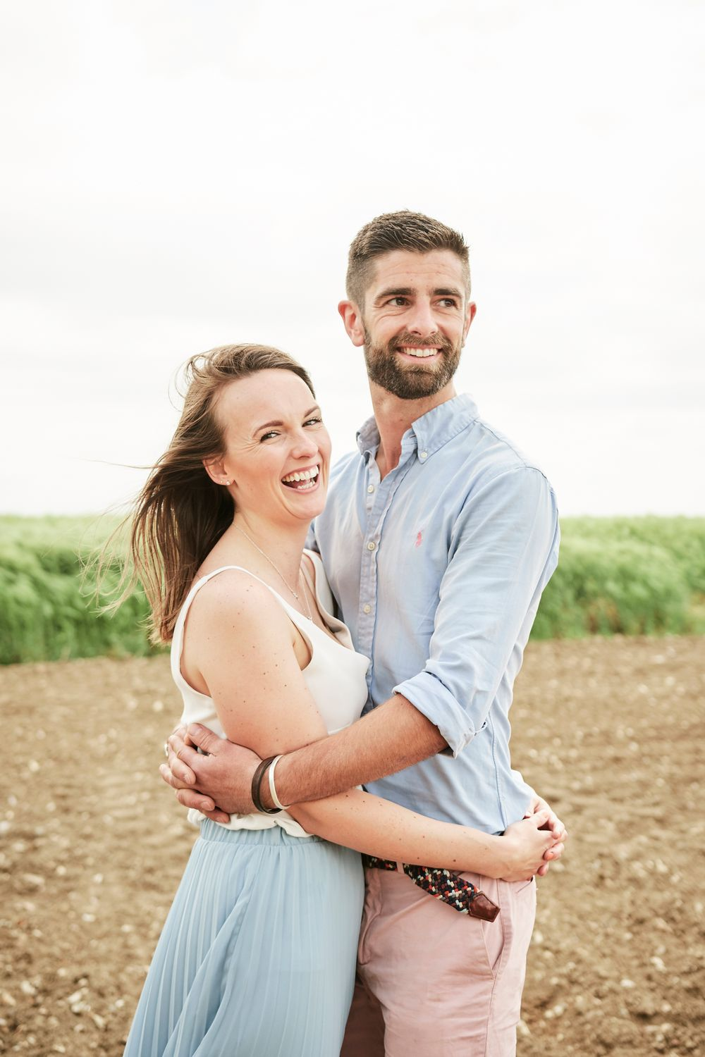 newly engaged couple share cuddle standing in farmers field by Norfolk wedding photographer Faye Amare