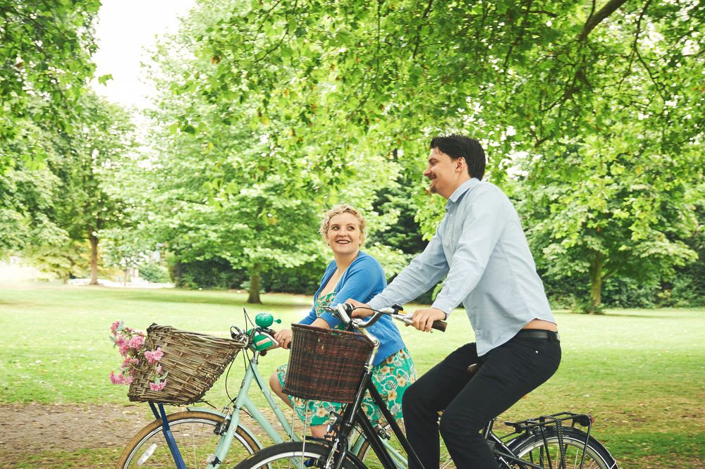 newly engaged couple ride bikes through Jesus Green Cambridge by norfolk wedding photographer Faye Amare