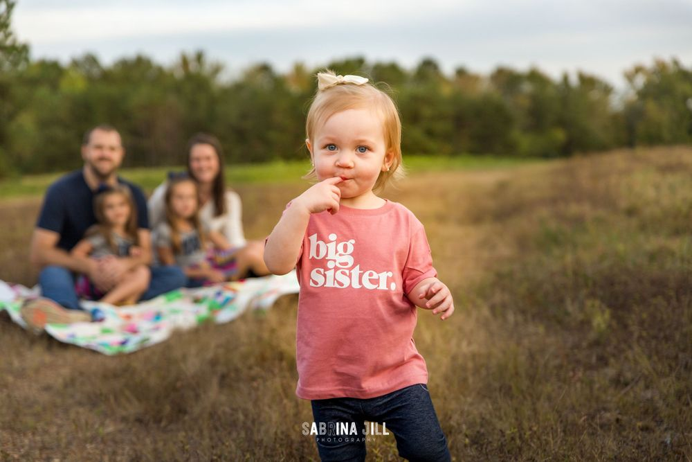 toddler wearing a big sister shirt in front of her family