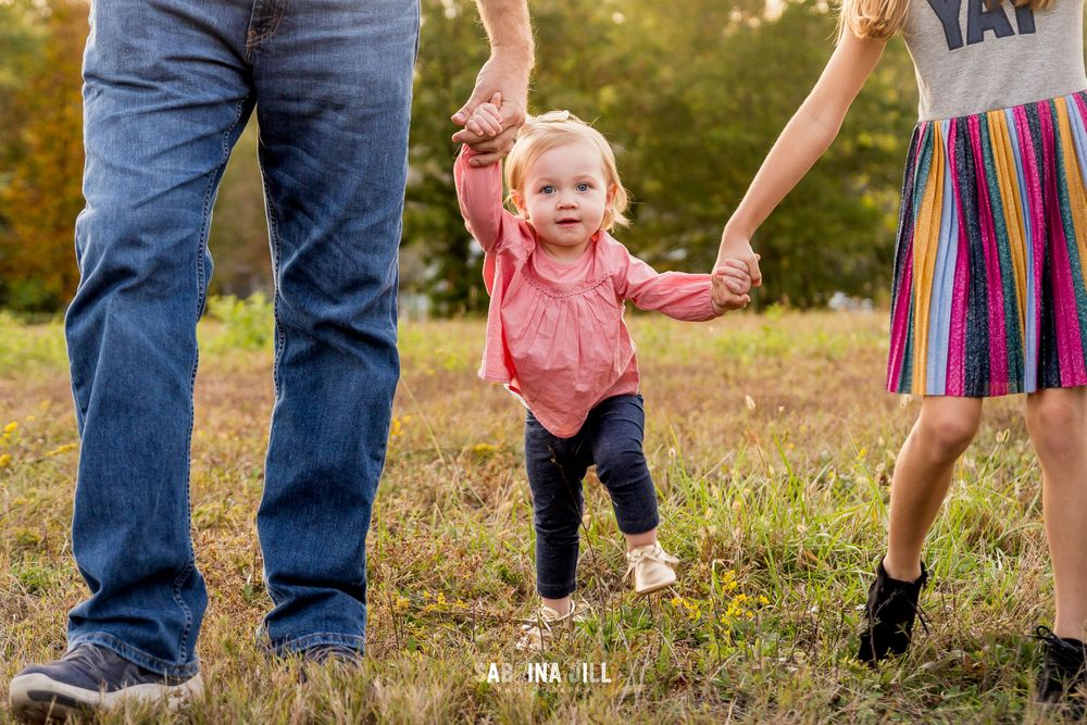 Toddler holding hands with dad and big sister in a field