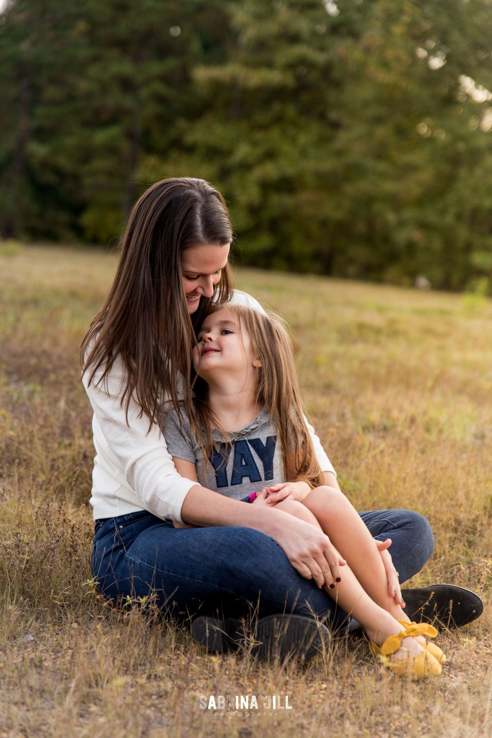 mother and daughter sitting together in a field