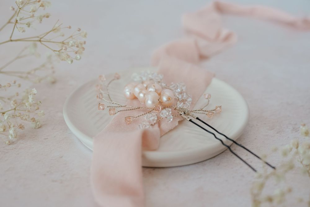 Pink hair pin on cream plate with pink ribbon and gypsophila