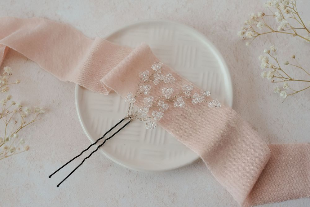 Clear bead hair pin on cream plate with pink ribbon and gypsophila