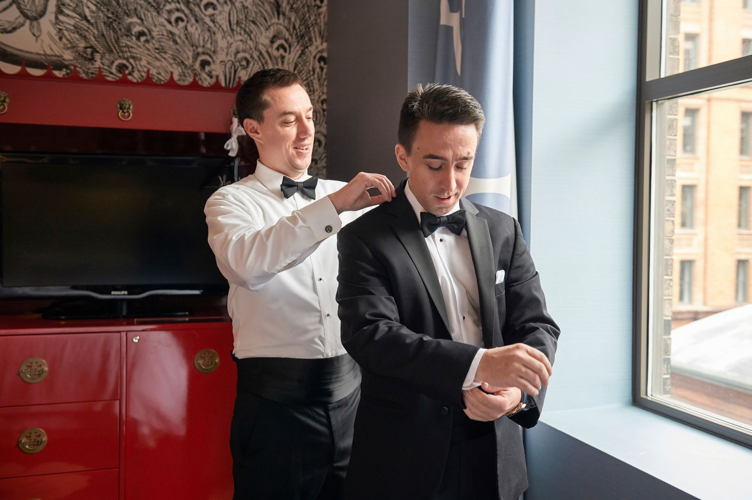 best man helping groom with jacket collar wedding photo
