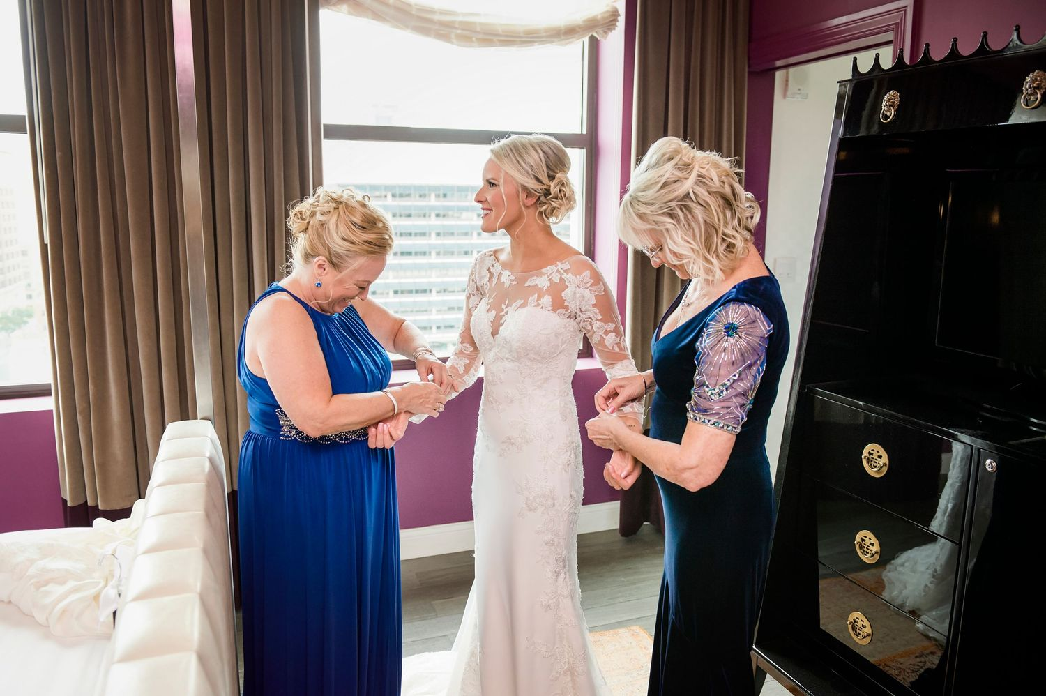 mother of groom and mother of bride helping bride get ready wedding photo