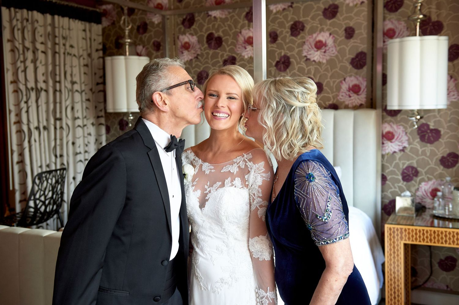 bride's parents kiss her on the cheek wedding photo