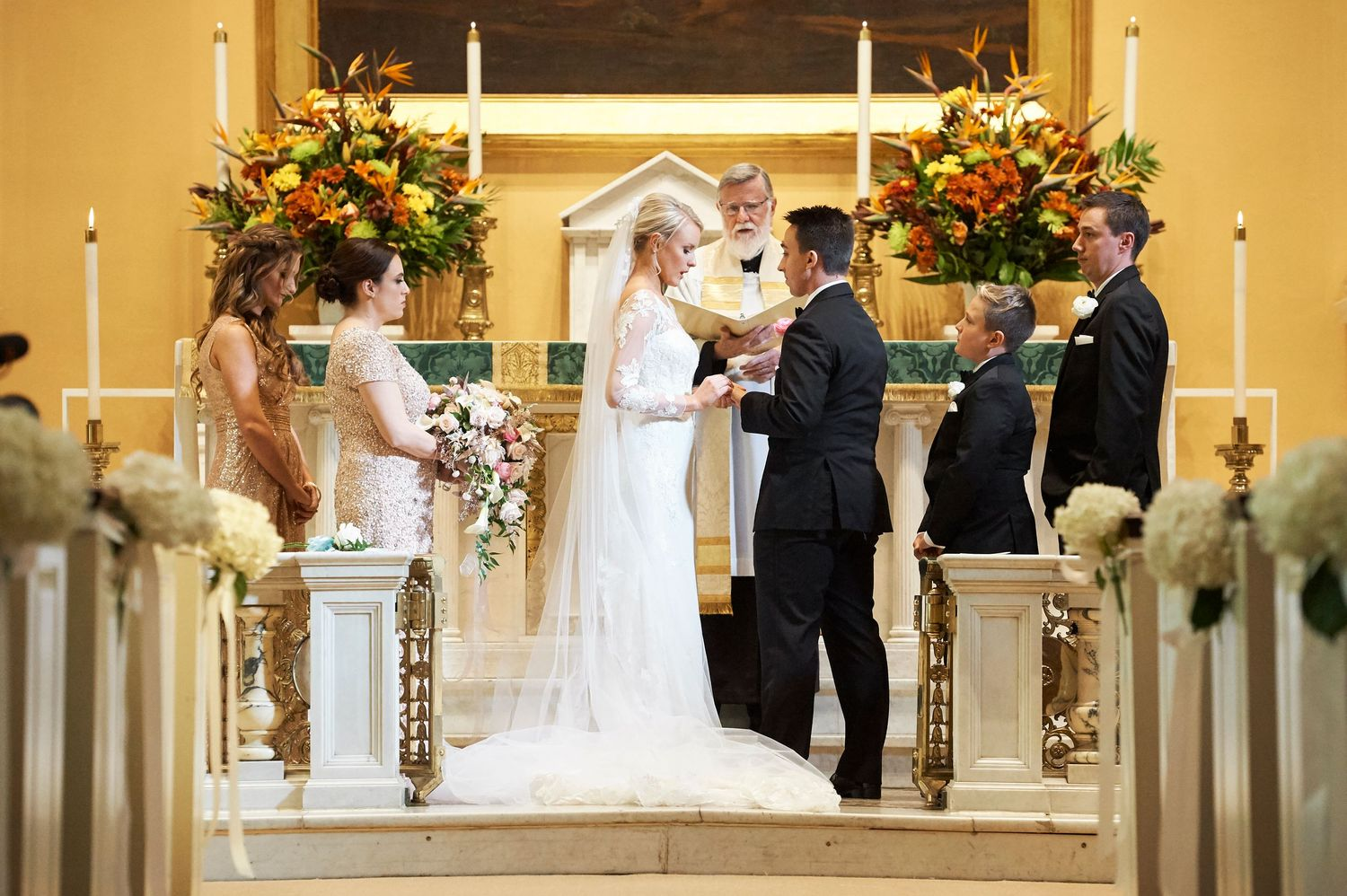 bride placing ring on groom's hand at Old St. Joseph's church in Philadelphia wedding photo