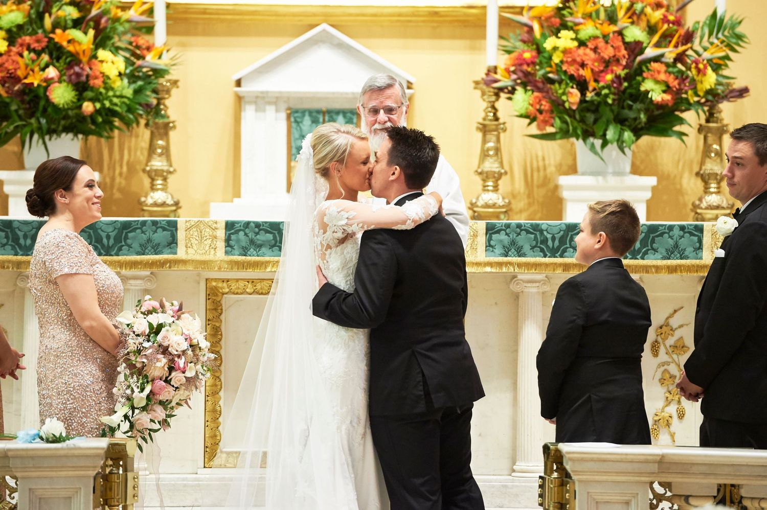 bride and groom's first kiss at Old St. Joseph's church in Philadelphia wedding photo