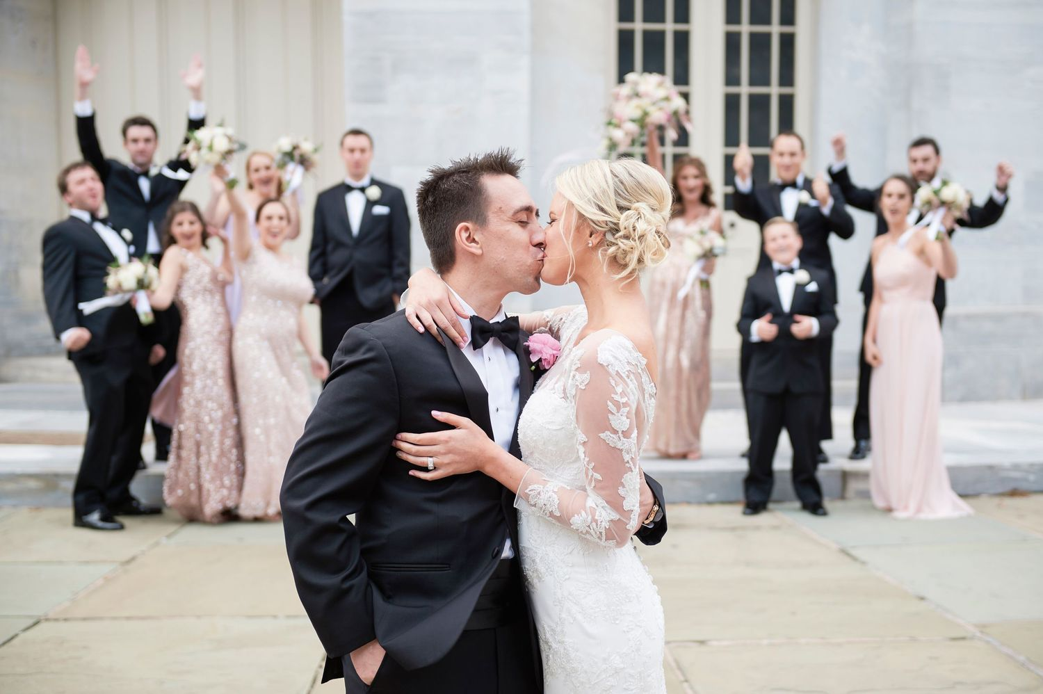 bride and groom kiss with bridal party cheering wedding photo at the Merchant exchange building in philadelphia
