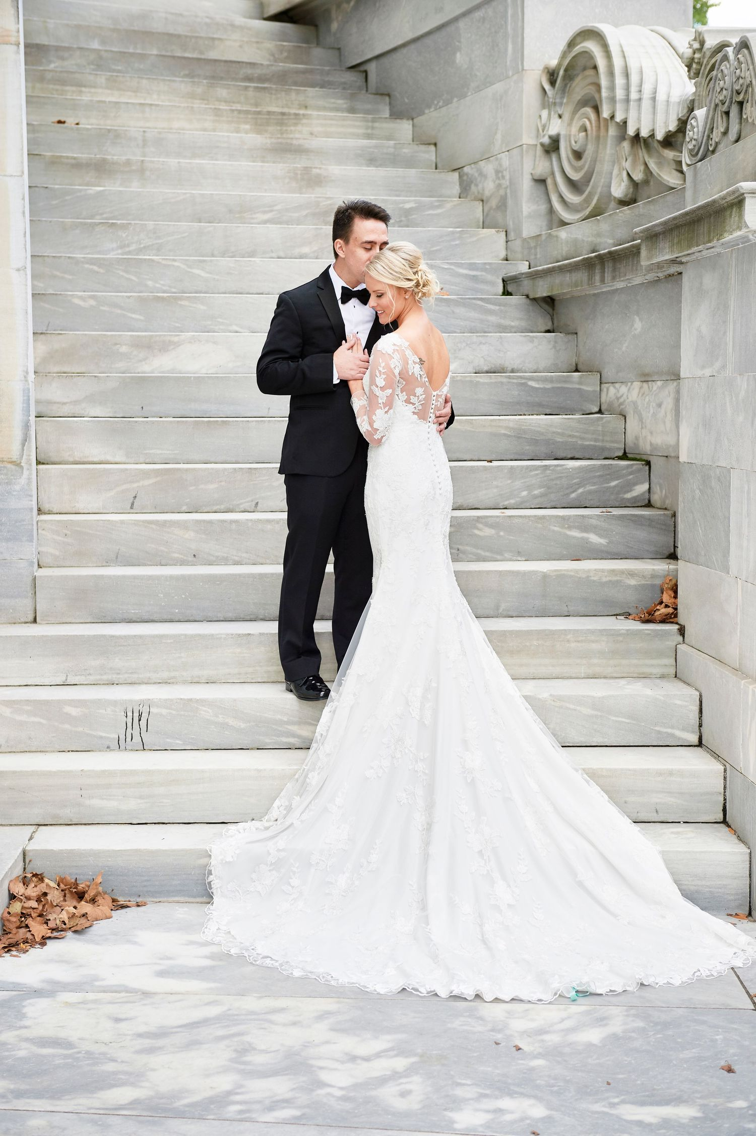 beautiful dress shot with bride and groom standing on stairs wedding photo at merchant exchange building in philadelphia