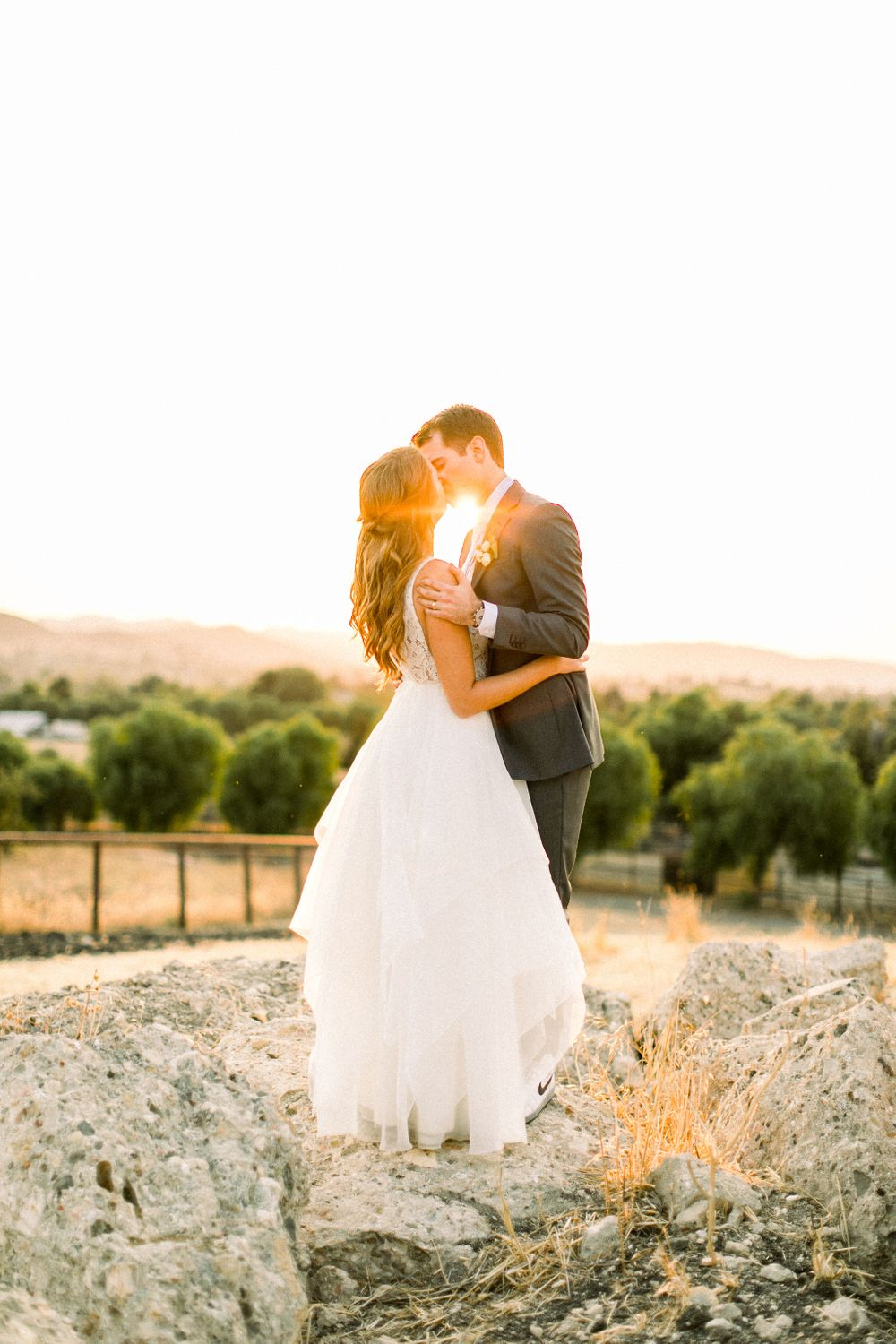 Married couple kissing at sunset at Pepper Tree Ranch