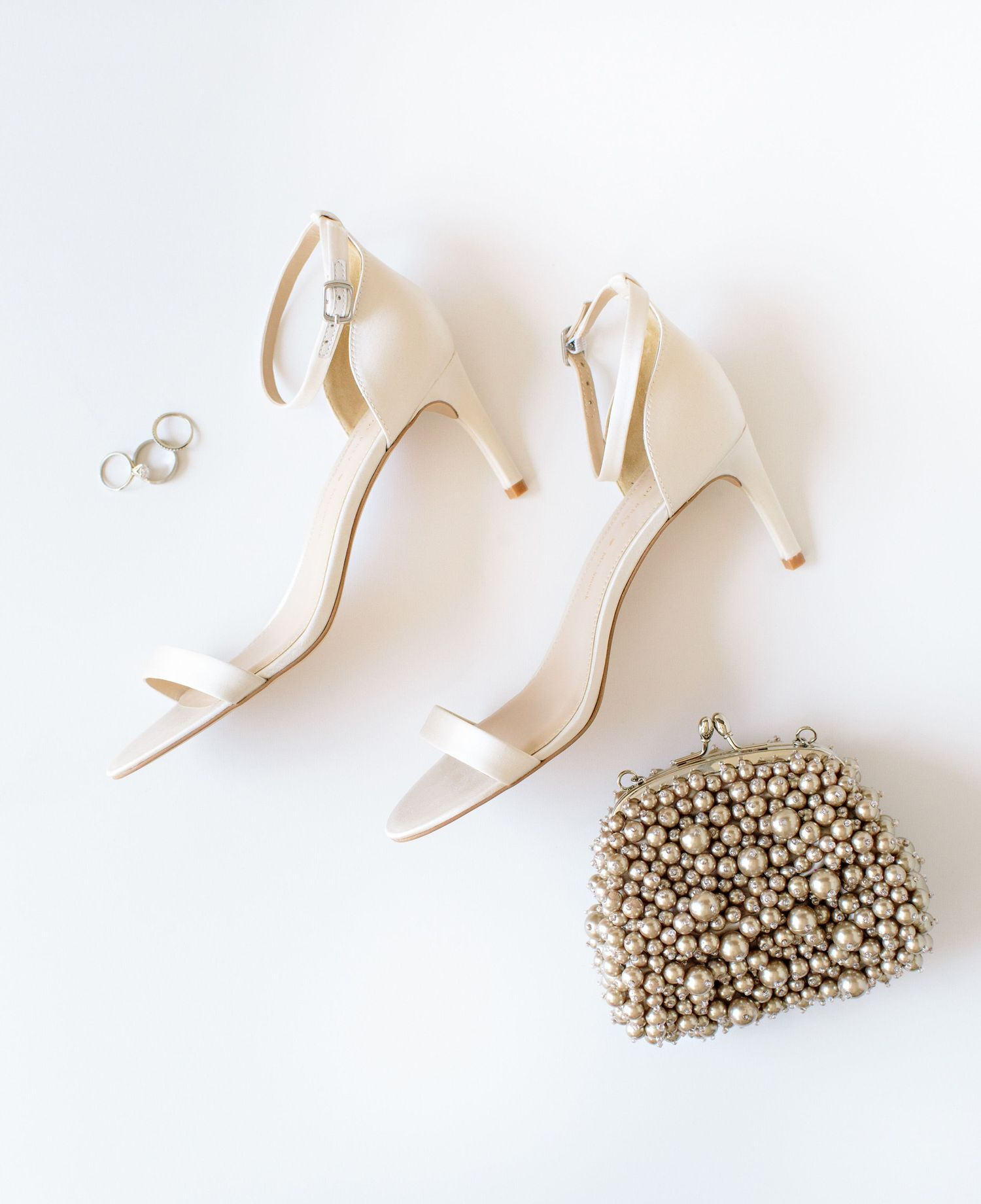 white shoes on white background with pearl purse and wedding rings