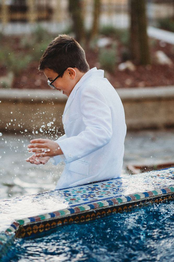 Portrait of a communion boy at a fountain